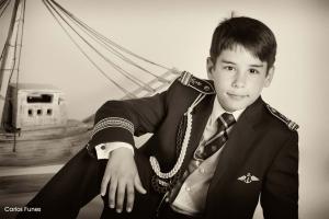 Rubén posando de traje de marinero junto a su barco