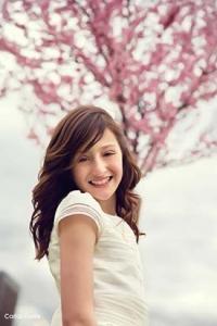 Paola vestida de primera comunión guapísima con un árbol al fondo