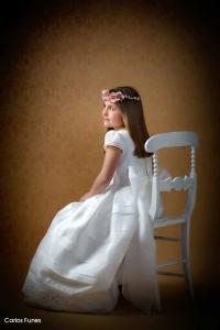 Alba posa sentada en una silla para las fotografías de su primera comunión