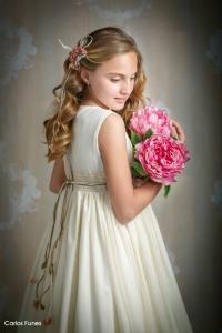 Lucia posa para las fotografías de Primera Comunión de espaldas en tres cuartos sujetando un ramo de flores rosas dejando lucir su precioso pelo dorado