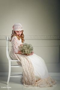 Lucia en una pose sentada sujetando un ramo de flores vestida de primera comunión firma Larrana