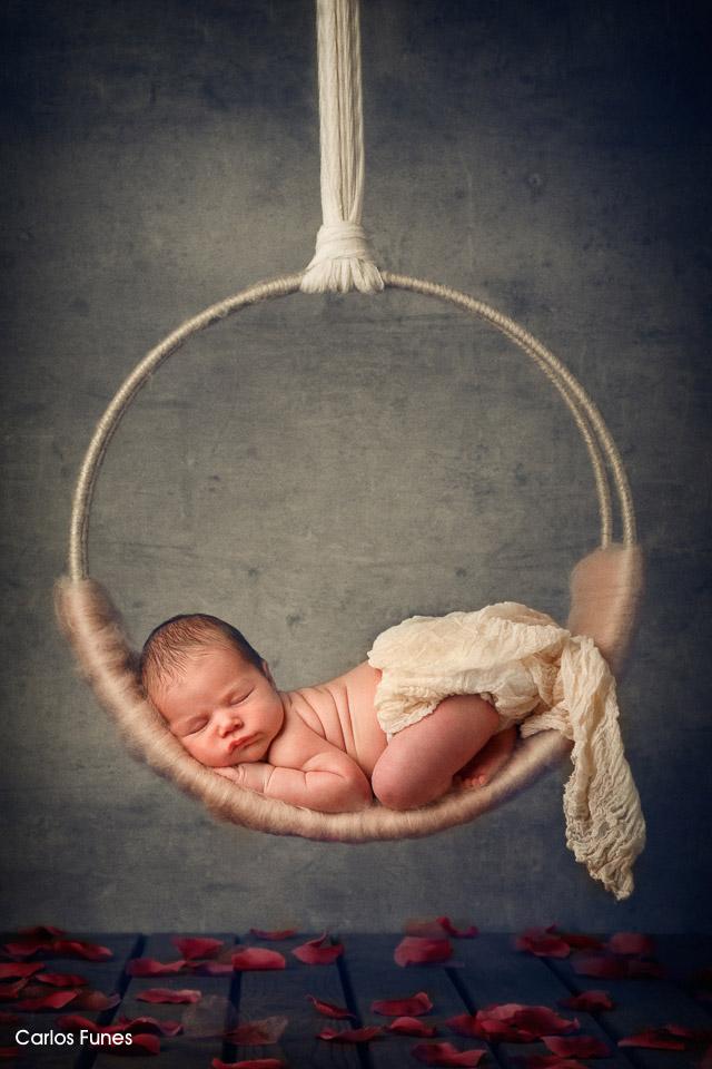 Fotografía de Marina. Una bebé preciosa que descansa sobre un aro colgado sobre un lecho de rosas. Fotografía por Carlos Funes. Especialista en retrato infantil y bebés.